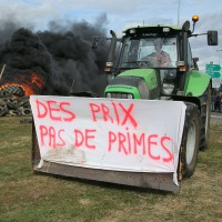 "French farmers gather in front of Lactalis' factory, Monday, July 27, 2015, in Laval, western France in order to protest against importation of foreign meat and milk products in France. The protests are a rejection of the government offer to back loans to the farmers and delay tax payments as part of a 600 million euro plan. Banner on the truck reads: ""Prices, no bonuses"". (AP Photo/David Vincent)/DAV106/19841323641/1507272001"