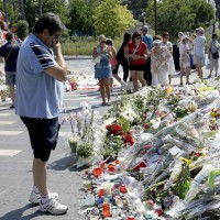 A man looks at flowers placed in a memorial near the Promenade des Anglais in Nice, southern France, Tuesday, July 19, 2016. Joggers, cyclists and sun-seekers are back on Nice's famed Riviera coast, a further sign of normal life returning on the Promenade des Anglais where dozens were killed in last week's Bastille Day truck attack. (AP Photo/Claude Paris)/CLP124/16201432735934/1607191410